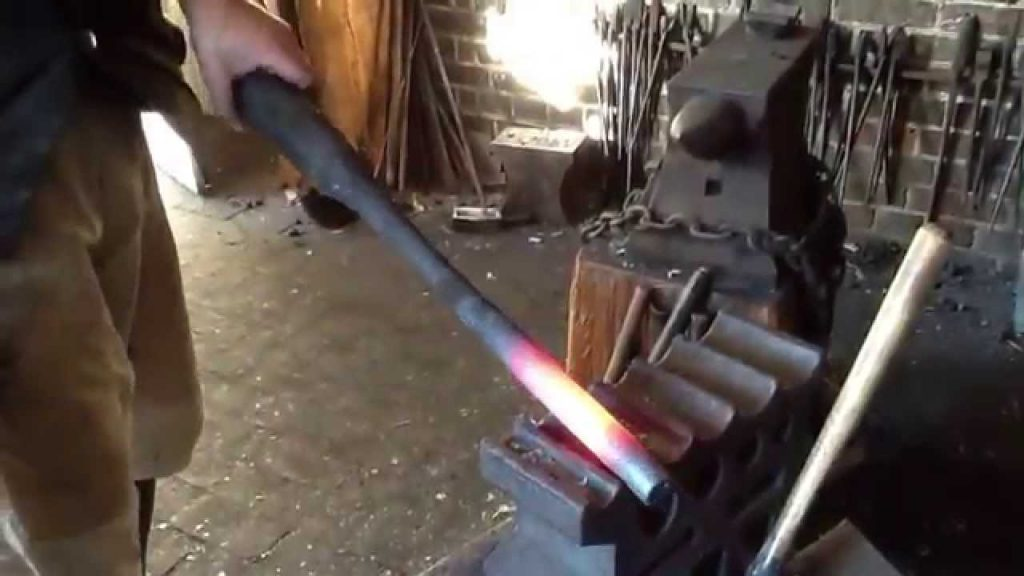 man forging the barrel of an ar15 in his work shed red hot