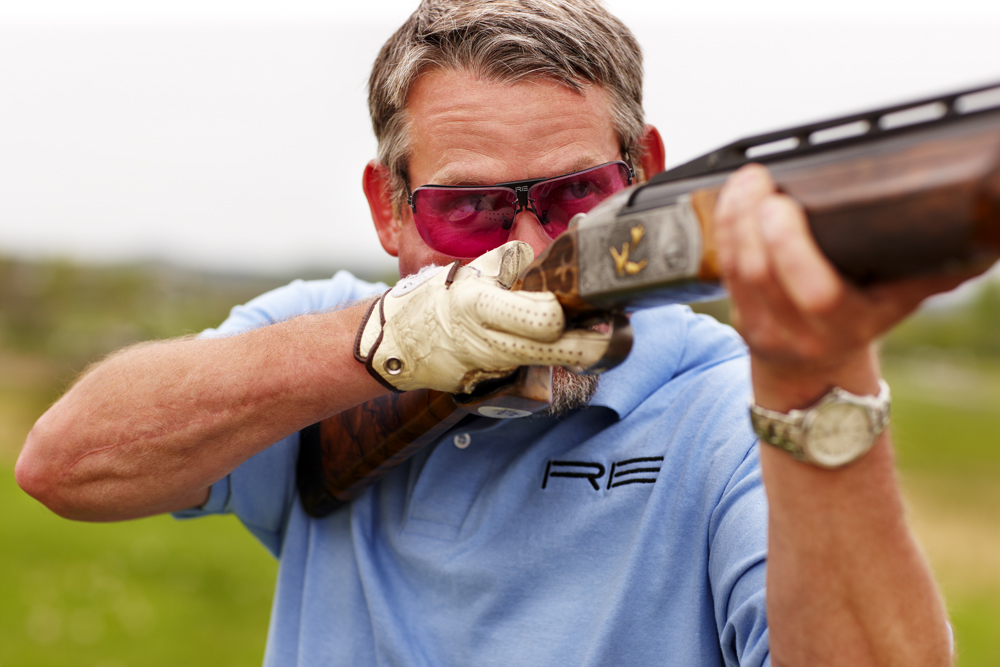 man holding a gun with glasses