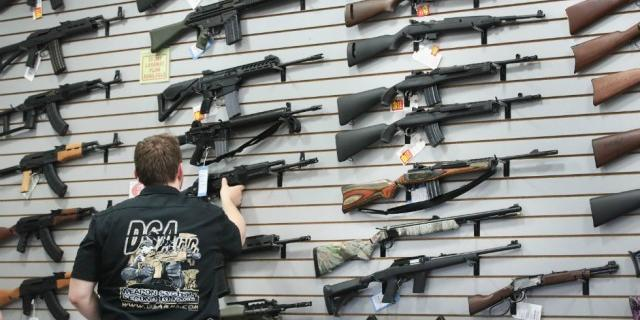 an image of a salesman with rifles in a store