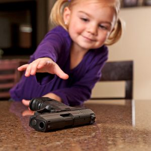image of a young girl reaching for the gun