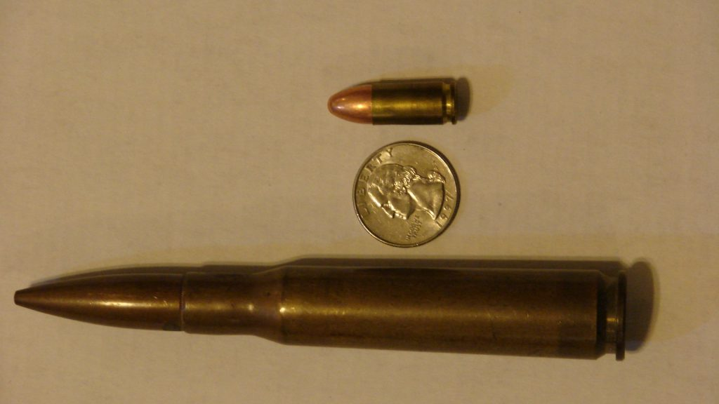 Image of a .50 BMG besides a penny and a 9mm bullet