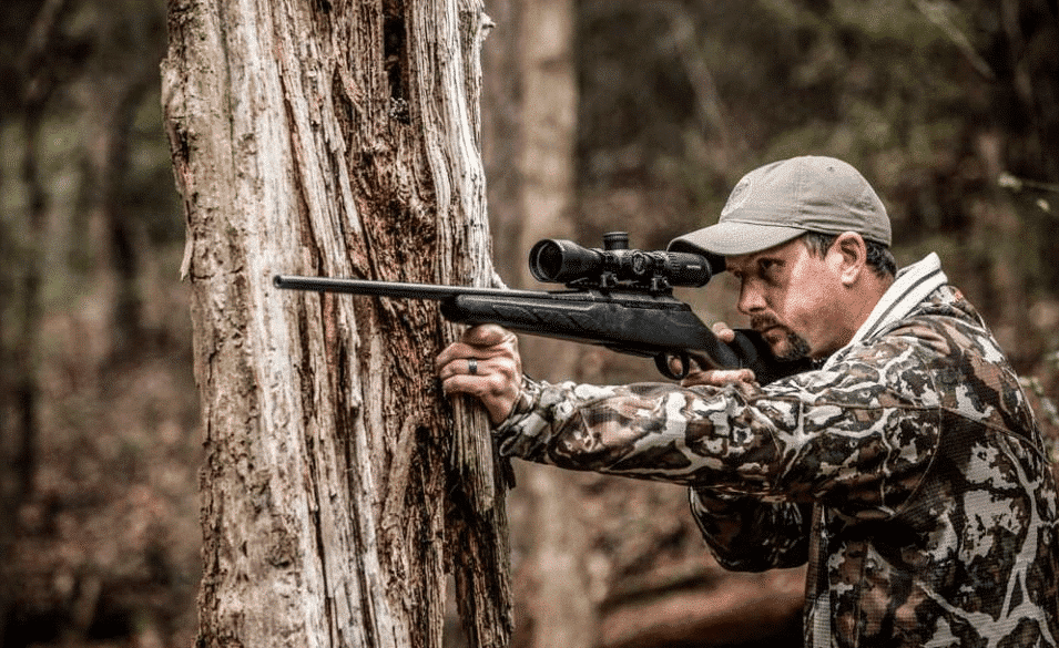 man shooting the Nightforce SHV 3-10x42mm Scope in the woods