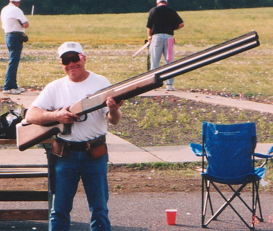 Picture of a man holding an extremely big rifle