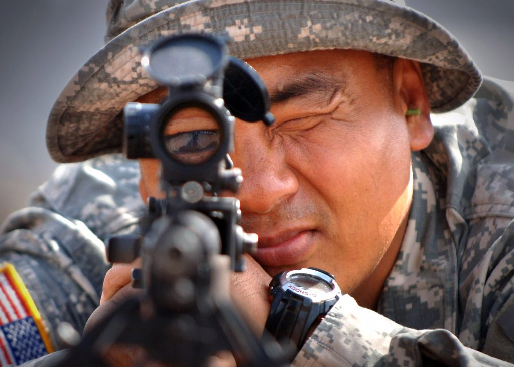 army sharpshooter aiming his rifle scope