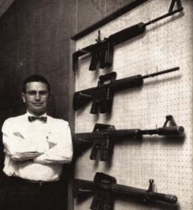 picture of eugene stoner standing next to a wall of ar15 rifles