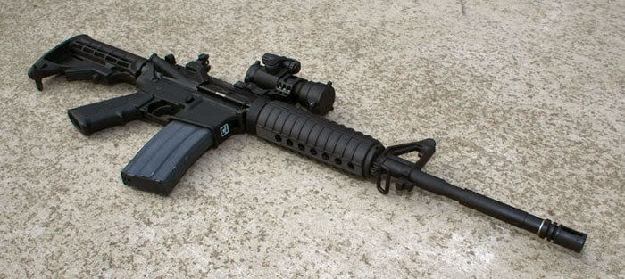 armalite ar15 a4 lying on its side on the ground, all black
