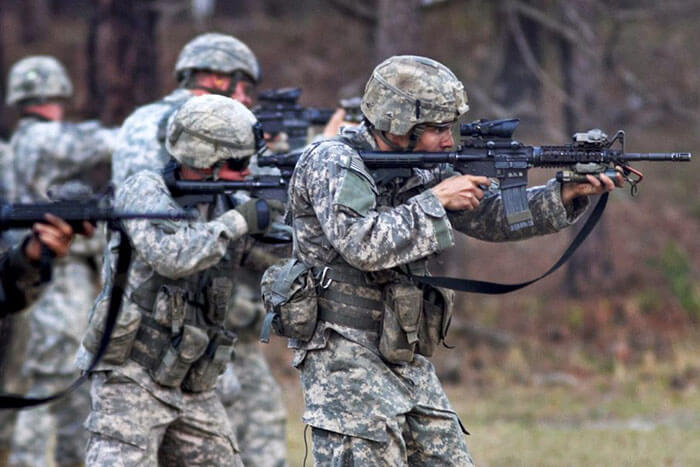 five army soldiers shooting ar15 rifles at the range during a training exercise
