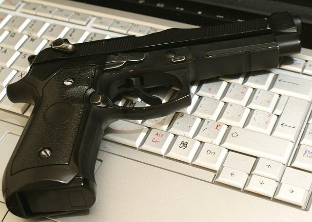 where to buy guns online - image of gun on a laptop keyboard