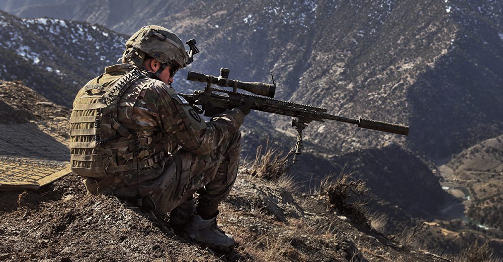 Image of a man in uniform sighting sniper rifle