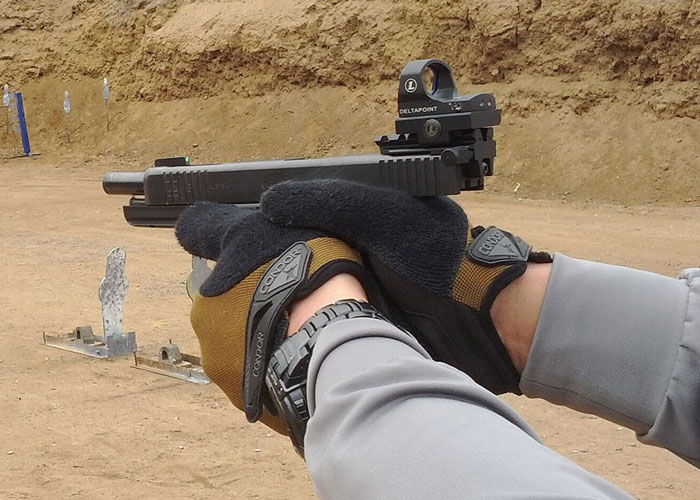 image of handling a gun with a black glock sight