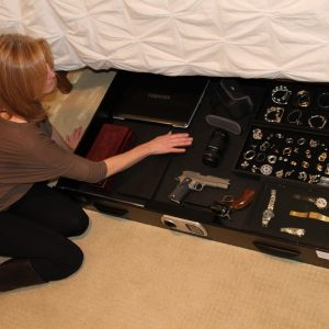 image of a women putting her gun and safe under her bed