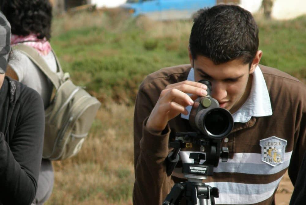 image of a man using OLYMPUS spotting scope