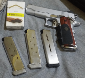 a picture of a hardchromed 1911 with three magazines