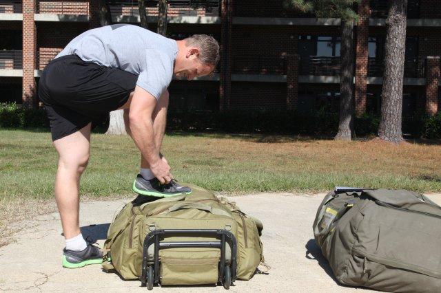 image of a man shoe lacing above a Pistol Bag