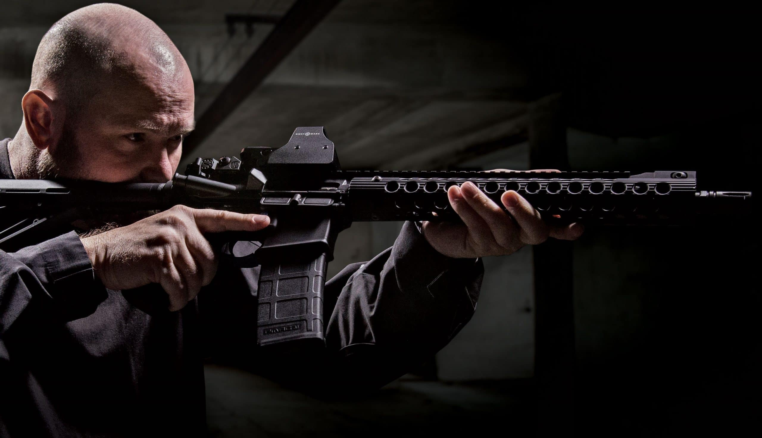 A picture of a guy holding an AR-15 with a Sightmark Ultra Shot mounted
