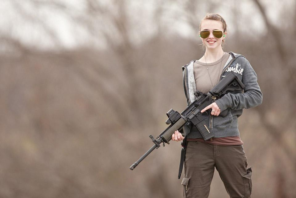 a girl pose her rifle