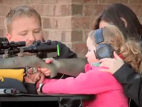 parents with their child teaching how to shoot