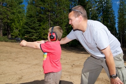 image of a young boy learning to shoot