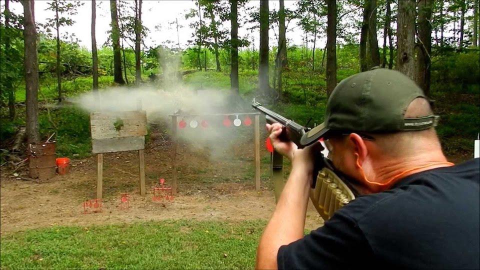 image of a man using a shotgun for target shooting