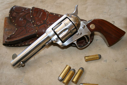 A picture of a Colt Single Action Army revolver with 45 Colt cartridges