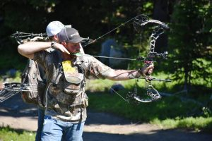 image of a man using his compound bow for hunting